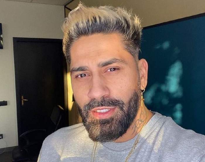 Connect-R își face un selfie. Artistul poartă un tricou gri și un lanț auriu la gât.