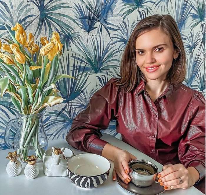 Cristina Siscanu poarta o camasa visinie de piele si sta la masa, cu o ceasca de ceai in fata
