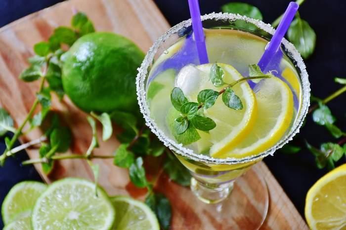 Imagine cu un pahar cu limonada cu menta si felii de lime pe langa