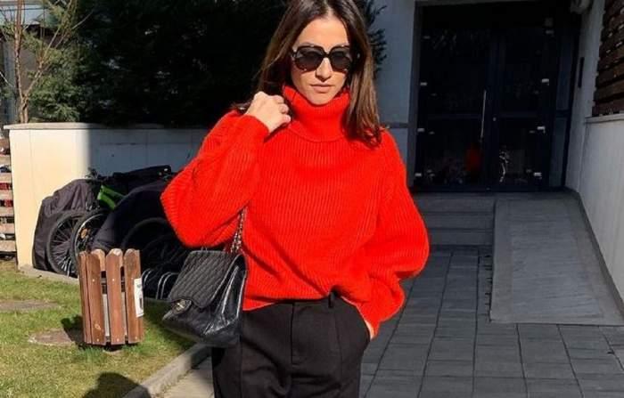 Claudia Pătrășcanu e îmbrăcată cu un pulover roșu și pantaloni negri. Artista are pe umăr o geantă neagră și poartă ochelari negri.