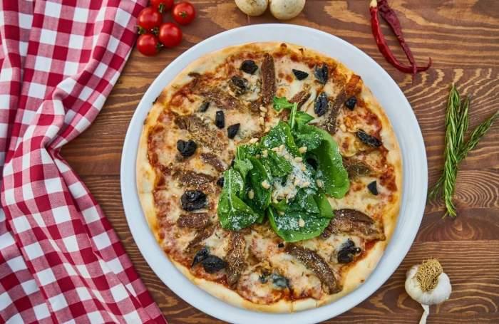 Imagine ilustrativa cu o pizza pusa pe o farfurie pe masa