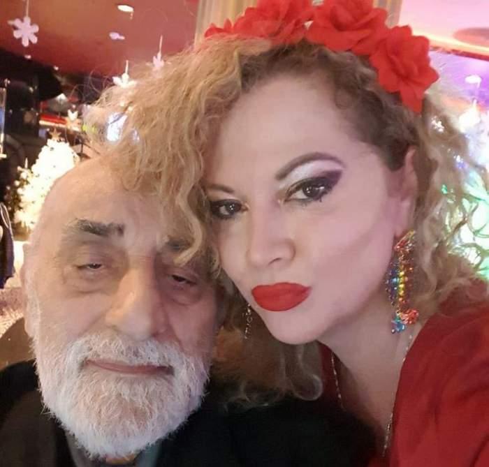 Oana și Viorel Lis se află la un eveniment. Ea poartă o bluză roșie și are niște flori în păr. Fostul edil poartă un costum negru.