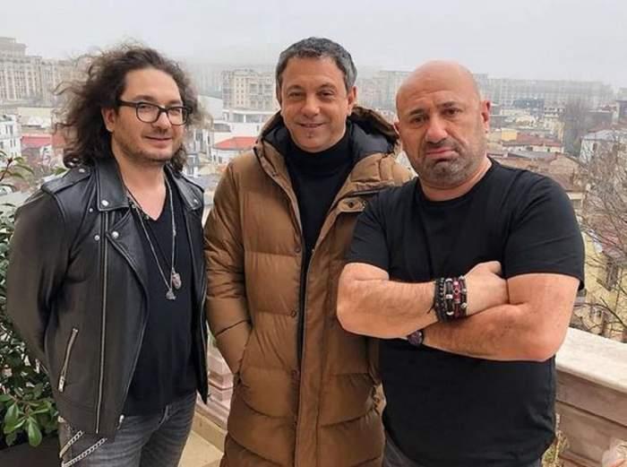 Cătălin Scărlătescu e alături de Florin Dumitrescu și Sorin Bontea. Cei trei se află afară, pe balcon. Cătălin poartă un tricou negru și are mâinile în sân, Florin poartă o geacă de piele neagră, iar Sorin o geacă maro.