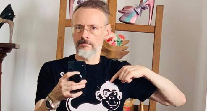 Mihai Albu își face o poză în oglindă cu telefonul. Creatorul de modă poartă un tricou negru pe care e desenată o maimuță albă și arată cu degetul spre ea.