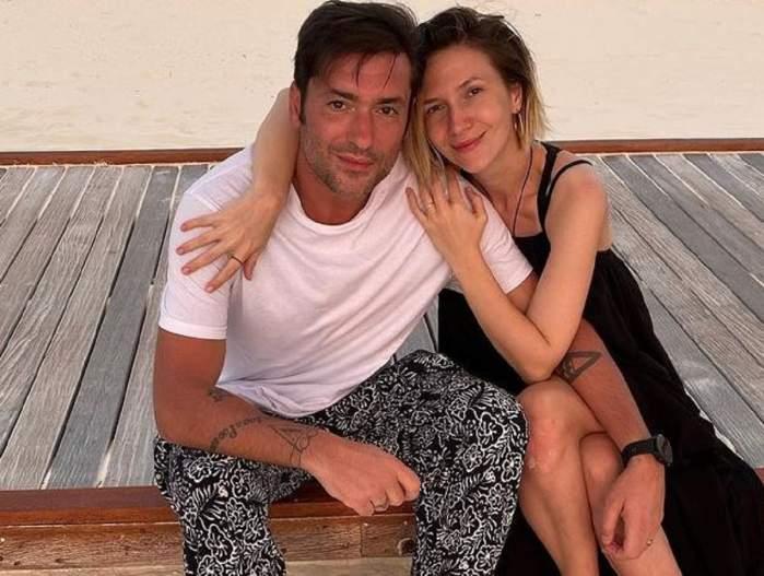 Radu Vâlcan și Adela Popescu pe plajă. Ea poartă o rochie neagră și îl ține în brațe, iar el un tricou alb și pantaloni negri cu model alb.