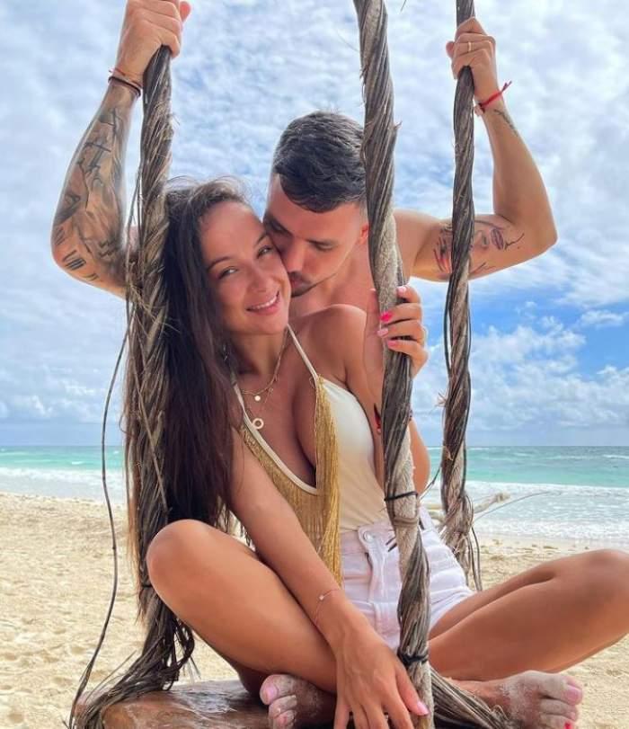 Vladuta Lupau sta intr-un balansoare pe plaja, in costum de baie, Adi Rus este in spatele ei si o saruta pe obraz
