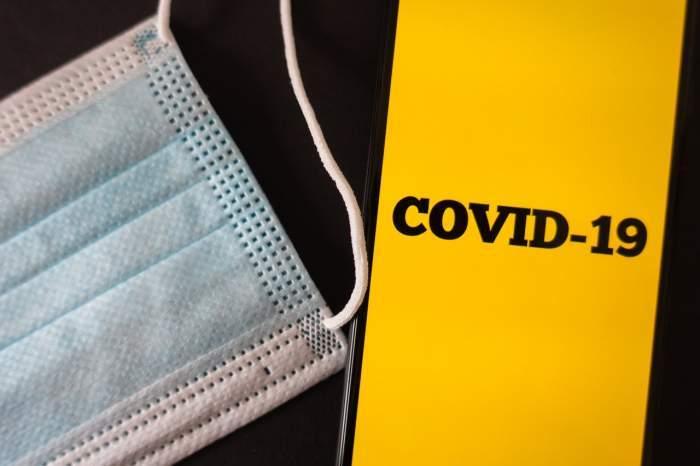 Imagine ilustrativa cu o masca de protectie si o aplicatie pe telefinul mobil pe care scrie Covid-19