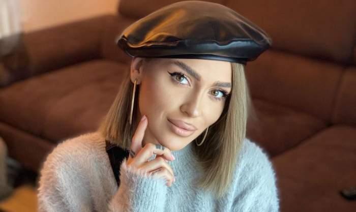 Oana Radu poartă o beretă neagră și un pulover gri. Vedeta zâmbește discret și își ține o mână la nivelul bărbiei.