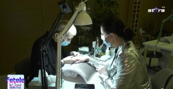Gabriela Cristeae la salonul de cosmetică. Vedeta poartă o geacă argintie, iar o angajată îi face unghiile.