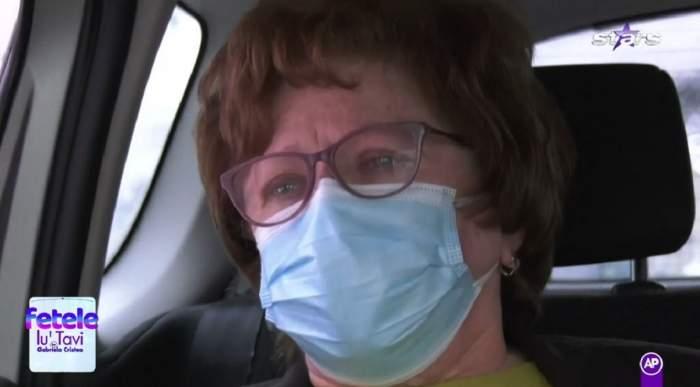Mama lui Tavi Clonda poartă ochelari de vedere și mască de protecție. Elena Clonda are ochii în lacrimi și e în mașină.