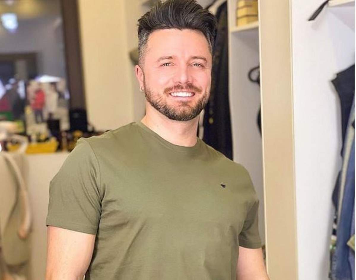 Tavi Clonda poartă un tricou verde. Artistul zâmbește larg.