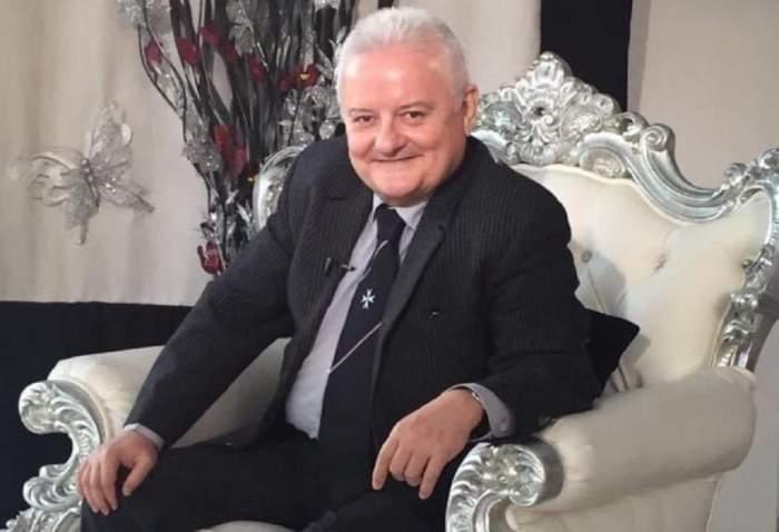 Irinel Columbeanu stă pe un fotoliu alb. Afaceristul poartă un costum negru și zâmbește.