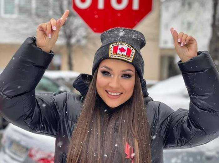Vlăduța Lupău poartă pe cap o căciulă neagră. Artista e îmbrăcată în geacă de iarnă neagră și ține mâinile deasupra capului, arătând spre un semn de circulație.