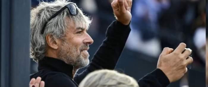 Petr Kellner poartă o bluză neagră și ochelari de soare negri pe cap. Miliardarul zâmbește și are o mână ridicată în aer.