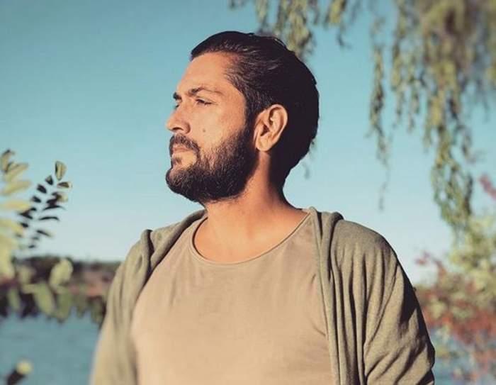Cezar Ouatu poartă un tricou crem. Artistul privește într-o parte. În spatele lui se văd mai mulți copaci și un lac.