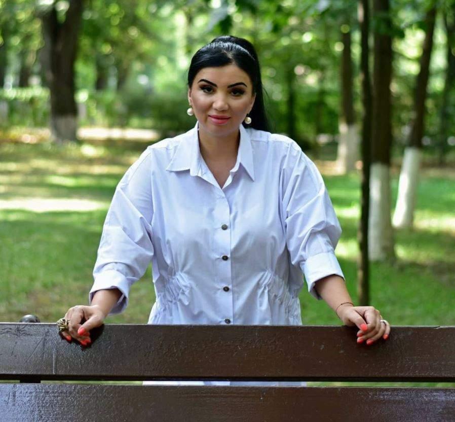 Adriana Bahmuteanu este in parc, este in spatele unei banci si poarta o camasa alba simpla