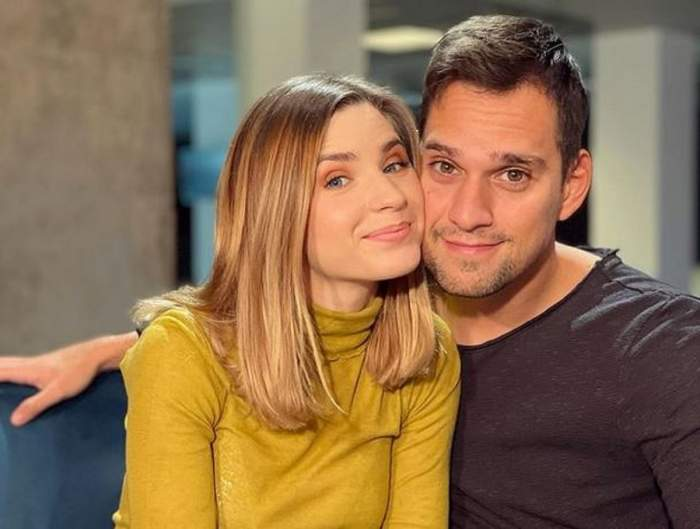 Cristina Ciobănașu și Vlad Gherman pe vremea când erau împreună. Stau pe o canapea albastră. El poartă o bluză gri închis, iar ea o maletă galbenă.