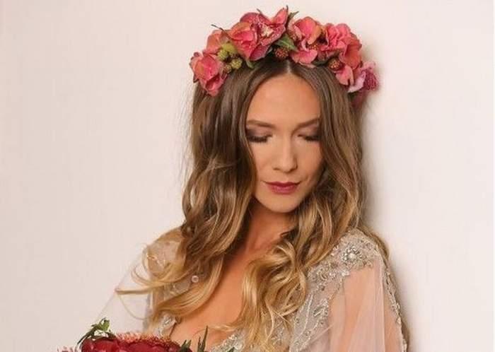 Adela Popescu poartă o rochie albă cu brațe din voal și are pe cap o coroniță de flori roz. Vedeta privește în jos.