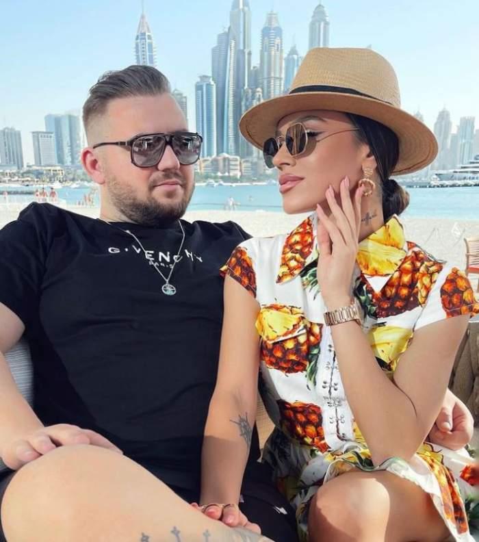 Karmen Simionescu este la o terasa in Dubai cu Bogdan Caplescu, ea poarta o rochie scurta cu palarie si ochelari de soare, el poarta haine negre si ochelari de soare