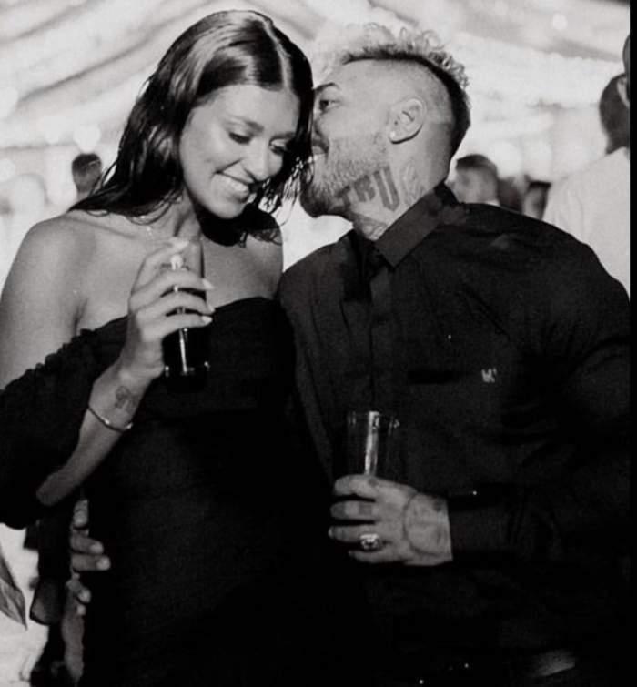 Antonia si Alex Velea sunt la o petrecere, au oahare de sampanie in mana, ea zambeste, el ii sopteste ceva la ureche