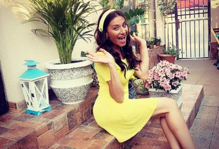 Claudia Pătrășcanu stă pe scări. Vedeta poartă o rochie galbenă, ține mâinile ridicate în aer și gura deschisă.