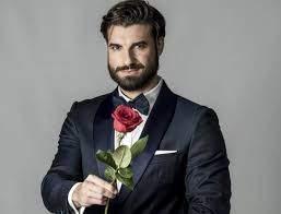 Andi Constantin, în costum negru, cu trandafir roșu în mână
