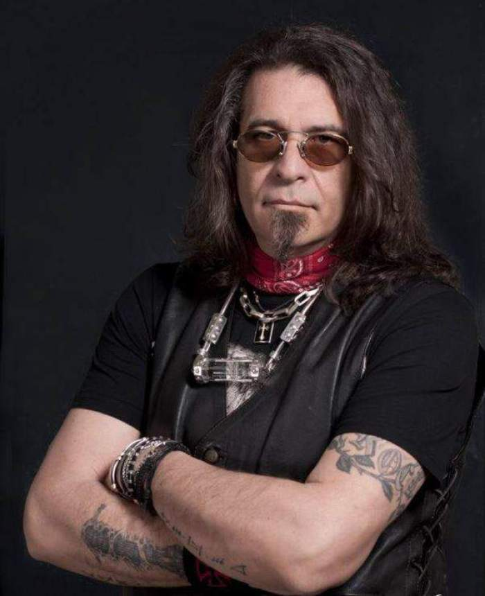 Adi Bărar, cu mâinile încrucișate, îmbrăcat în negru, cu ochelari