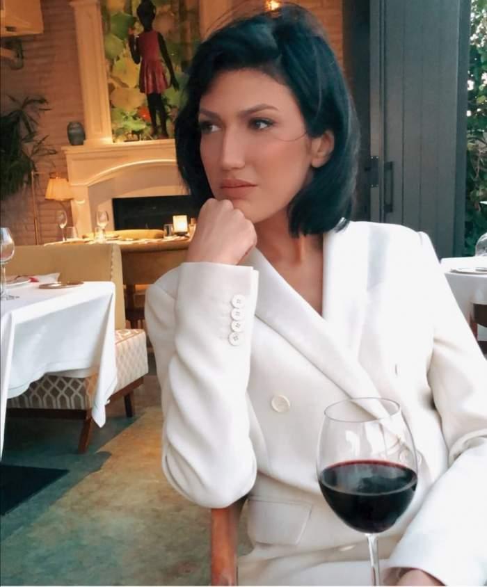 Daliana Răducan, îmbrăcată în alb, cu un pahar de vin în față