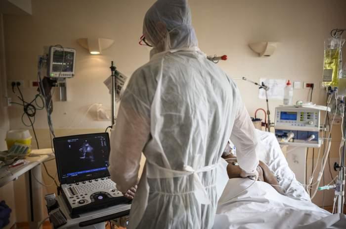 Un medic î combinezon consultă un pacient