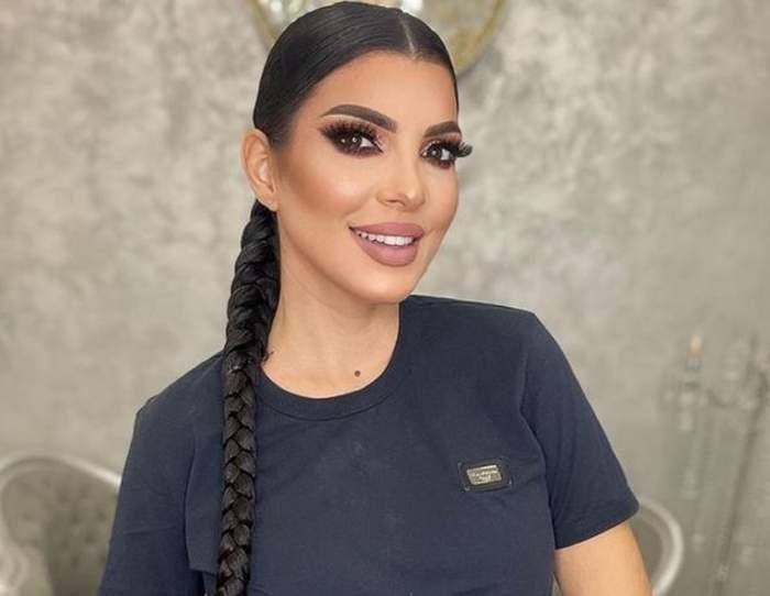 Andreea Tonciu poartă un tricou negru. Vedeta zâmbește larg.