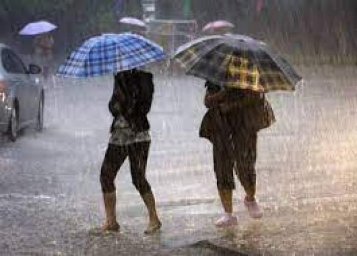 Două persoane care merg prin ploaie , cu umbrele în mână