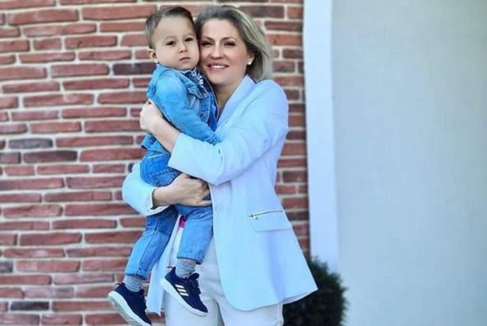 Mirela Vaida poartă un costum bleu și zâmbește. Vedeta îl ține în brațe pe Tudor, fiul ei cel mic, care e îmbrăcat într-un costum de blugi.