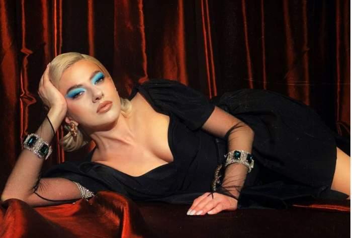 Lidia Buble este intinsa pe canapea rosie, poarta rochie neagra