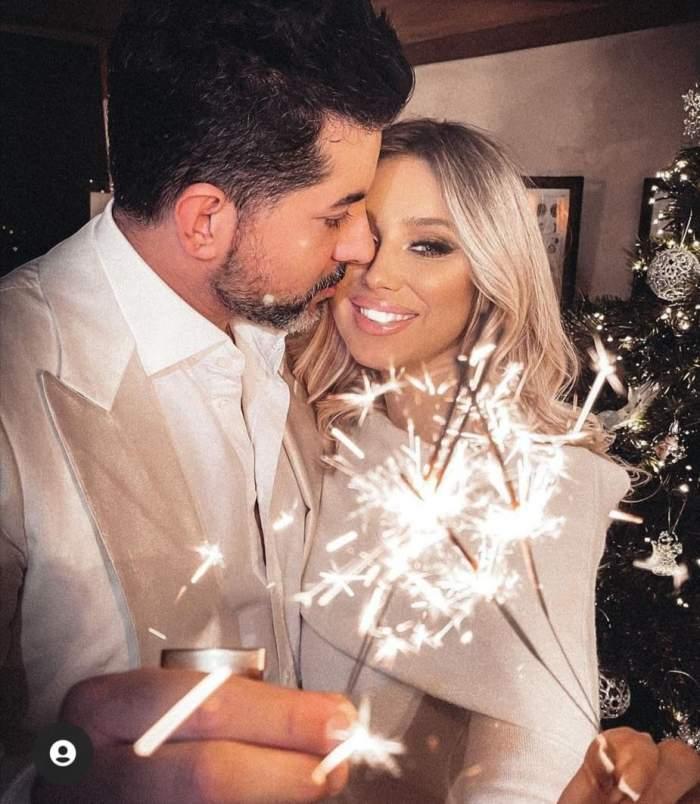 Ela Arjandas și soțul, îmbrăcați în alb, se sărută, cu artificii în mână