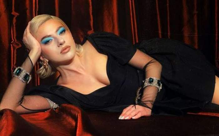 Lidia Buble în rochie neagră, întinsă pe pat.
