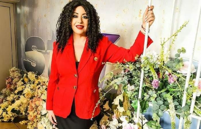 Oana Roman e îmbrăcată cu o rochie neagră, iar pe deasupra cu un sacou roșu. Vedeta poartă perucă neagră, creață, zâmbește și se ține cu mâna de o țeavă albă.