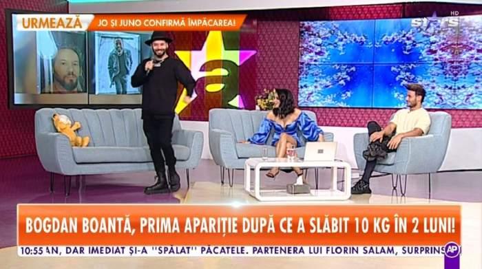 Bogdan Boantă e la Antena Stars. Dansatorul e îmbrăcat în bluză și pantaloni negri și are pe cap o pălărie neagră. Coregraful stă în picioare și ține microfonul în mână.