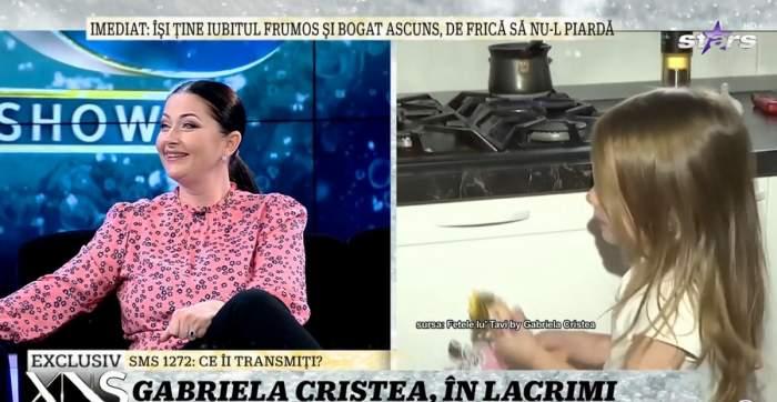 Gabriela Cristea e la Xtra Night Show. Vedeta poartă o bluză roz și pantaloni negri. Prezentatoarea zâmbește larg.
