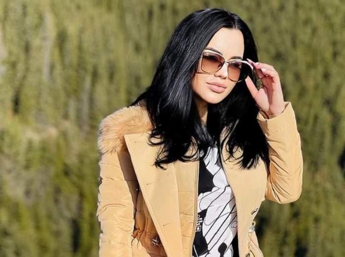 Carmen de la Sălciua se află afară. Artista poartă ochelari de soare, un tricou negru cu alb, iar pe deasupra are o geacă stil sacou de culoare crem.