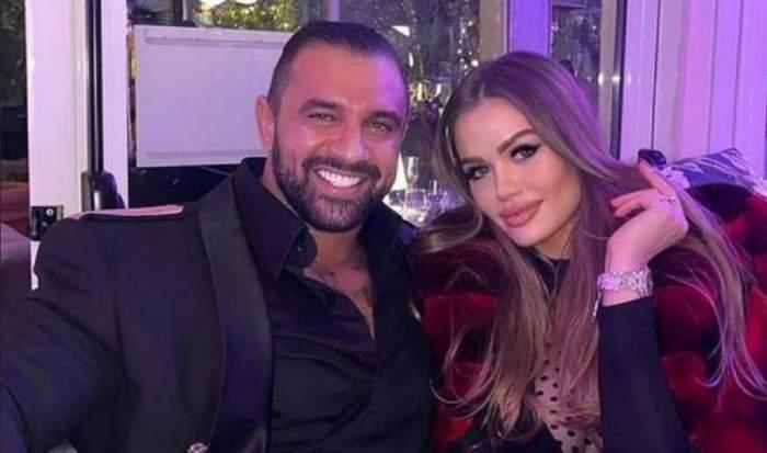 Daria Radionova și Alex Bodi stau pe o canapea, unul lângă altul. Ea poartă o haină de blană roșie, iar el un costum bleumarin.