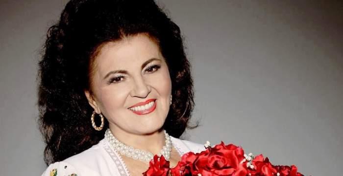 Irina Loghin poartă o bluză albă. Artista ține în brațe un buchet mare de flori roșii și zâmbește.
