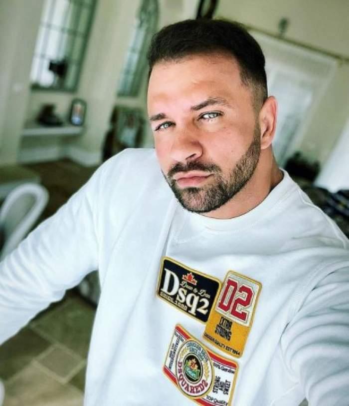 Alex Bodi în bluză albă, în casă.