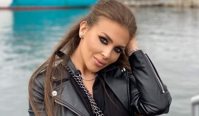 Oana Radu poartă o geacă de piele neagră și zâmbește, având o mână prin păr. În spatele ei se vede marea.