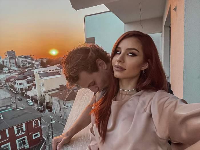 Carmen Grebenișan și iubitul, care o sărută pe umăr, s-au fotografiat pe balconul viitoarei locuințe