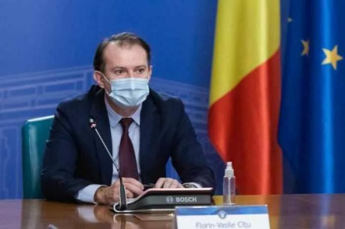 Florin Cîțu, în costum negru, cu masca de protecție pe față