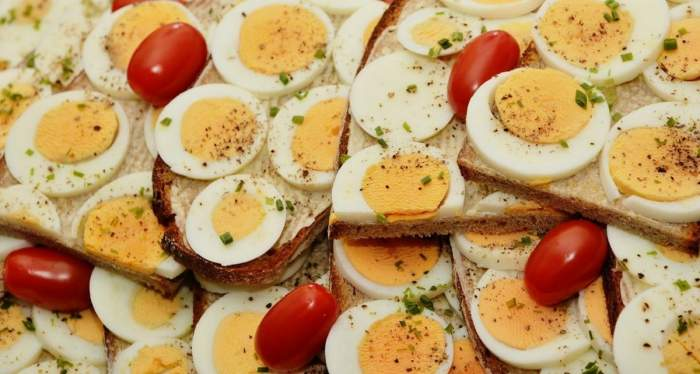 Un preparat cu ouă fierte. Acestea sunt servite cu pâine și roșii.