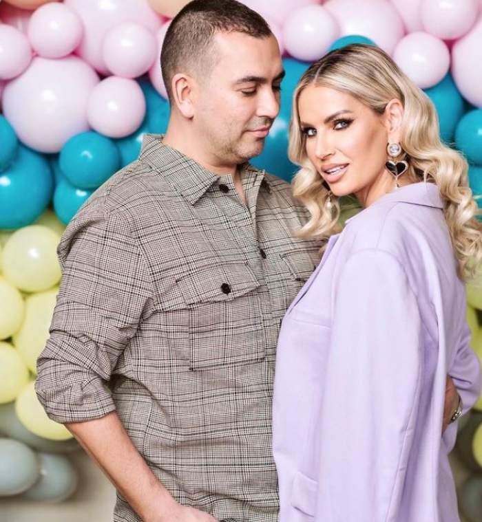 Andreea Banica si Lucian Mitrea sunt langa un panou cu baloane, sunt imbracati elegant, el se uita la ea