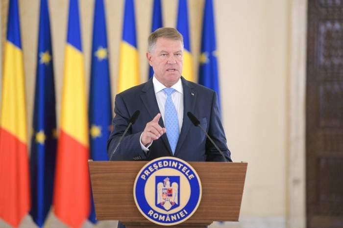 Klaus Iohannis ține un discurs. Președinte poartă cămașă albă, cravată bleu și sacou albastru.