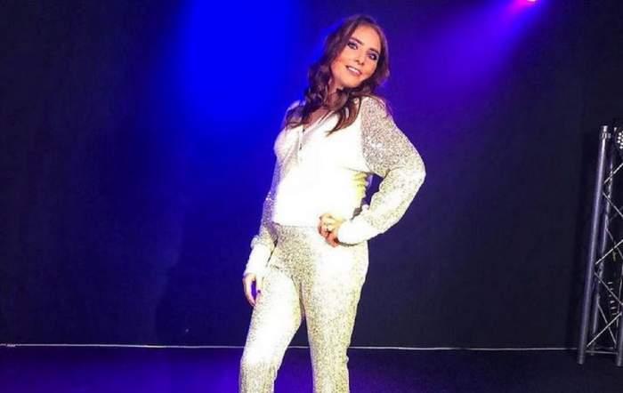 Vulpița de la Acces Direct poartă un costum alb, format dintr-o bluză și pantaloni cu paiete. Veronica Stegaru zâmbește și ține o mână în șold.