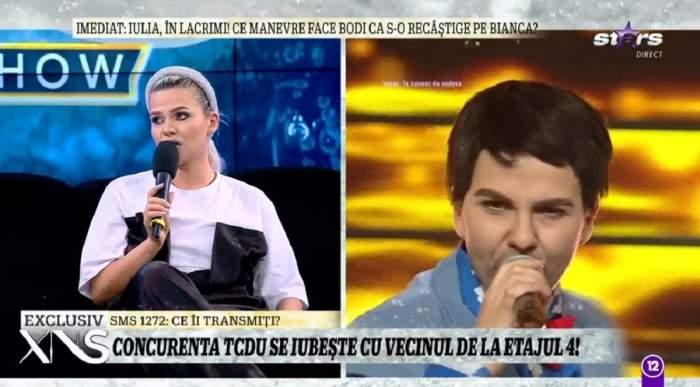 Cristina Vasiu e pe canapea la Xtra Night Show. Vedeta vorbește la microfon și poartă un tricou alb și o salopetă neagră.